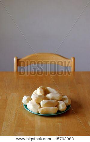 Peeled potatoes sitting on dinner table