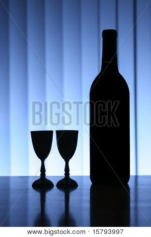 Wine bottle with two glasses, dramatic light, copy-space for text.