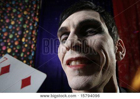 Smiling Joker face. Dramatic light.
