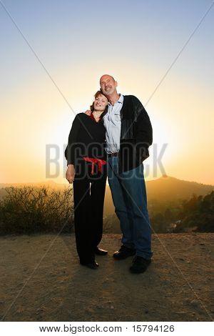Casal feliz abraçando no exterior ao pôr do sol