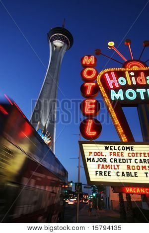 Neon motel sign and Stratosphere hotel and casino tower at dusk in Las Vegas, Nevada, USA