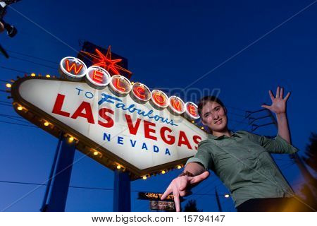 Happy young woman in front of Welcome To Las Vegas Sign, Las Vegas, Nevada, USA