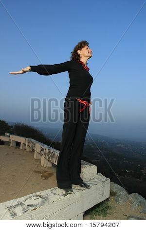 Happy mature woman doing exercises outdoors ontop of city.