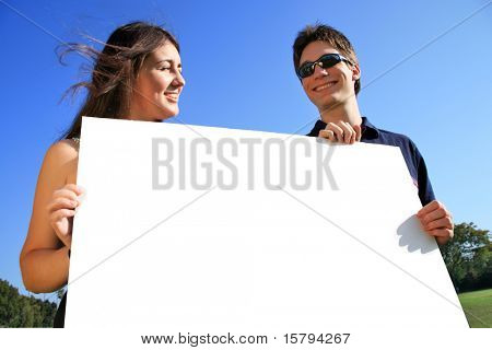 Young couple holding a blank white billboard outdoors