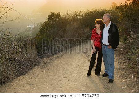 Casal maduro, apreciando o pôr do sol em uma pista ao ar livre.