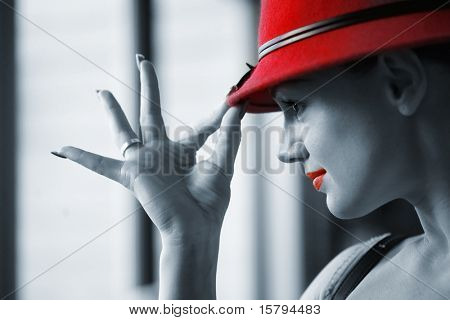Beautiful young woman in red hat posing. Shallow DOF.