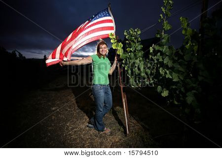 Young woman standing with American flag next to grape plant in Napa Valley at dusk.