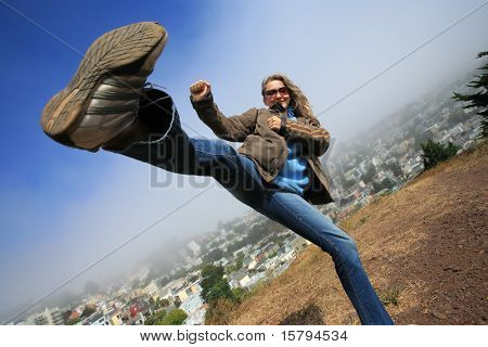 Young woman fooling around doing high kick ontop of the Kite Hill, San Francisco, California, USA.