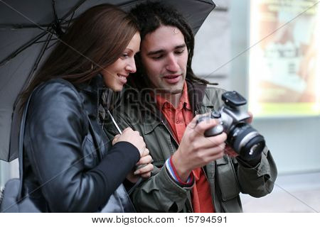 Young couple under umbrella, looking at digital SLR camera, smiling. Selective focus.