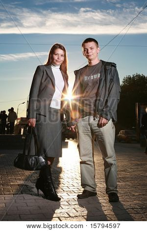Retrato de una situación de la joven pareja en una calle cogidos de la mano al atardecer.