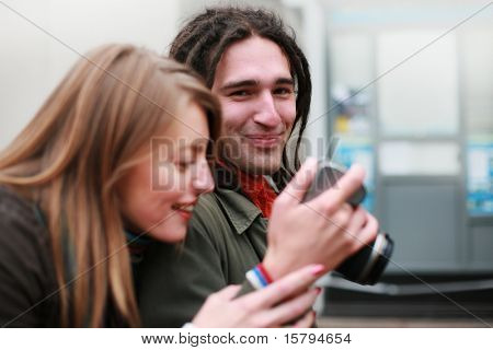 Young man showing digital photos on his camera to beautiful woman while walking down a street.