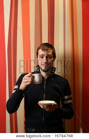 Cool young man with cup of tea or coffee.
