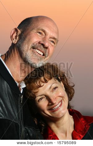 Loving senior couple portrait at sunset. Shallow DOF, focus on woman.