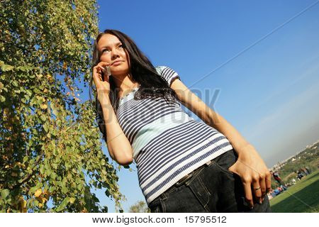 Beautiful girl talking on cell phone outdoors