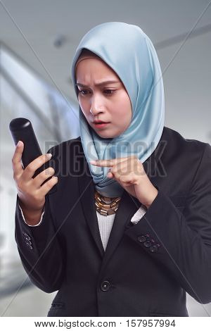 angry businesswomen while pointing her finger to the phone in blur background