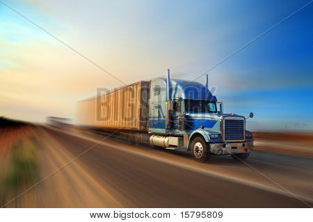 American truck speeding on freeway at sunset, motion blurred.