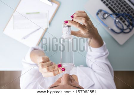 Top view of a close up of a female doctor is inhaling the medicament from the pressurized cartridge inhaler placed on an inhalation chamber on a medical demonstration on her medical desk - Medical respiratory disease