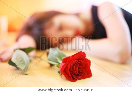 Lonely young woman with red rose. Shallow DOF, focus on flower.