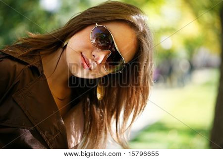 Portrait of a beautiful young woman in autumn park.