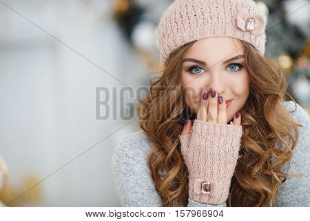 Portrait of beautiful redhead young woman with blue eyes and curly long hair,in a beige knitted cap and gloves,beautiful makeup and large black eyelashes,purple nail Polish,posing in Studio on light background ornate Christmas tree with yellow balls