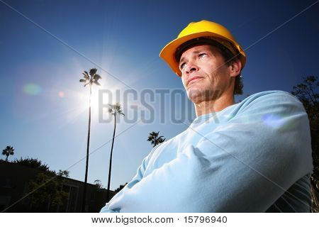 Construction worker in yellow hard hat over blue sunny sky