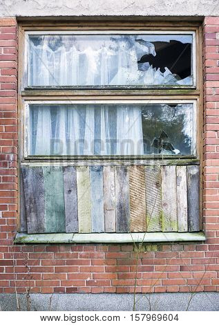 Window boarded up by wooden panels in an old red brick house with beat all glass