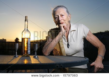 Elderly woman sitting at the table with bottle of white wine outdoors at sunset.