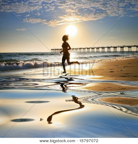 Woman at the beach running by the ocean at sunset