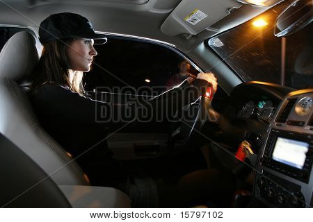 Beautiful young woman driving car at night