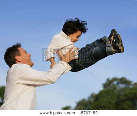 Father lifting son in the air. Shallow DOF.