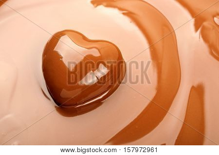 closeup of chocolate heart on melted chocolate surface