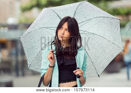 Thinking asian girl city portrait. Serious sexy woman outside with umbrella and glasses in casual business suite. Beautiful young mixed race Asian Caucasian woman.