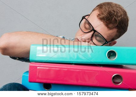 Young sleepy student in glasses with folders. sleeping on the folders. isolated gray background