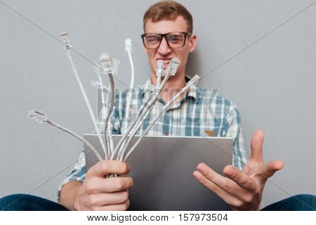 Young student in glasses with laptop and cables. front view