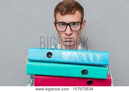 Serious hipster in glasses with folders looking at camera. isolated gray background
