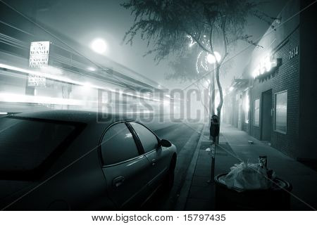 Bus speeding through foggy night street. West Hollywood, California.
