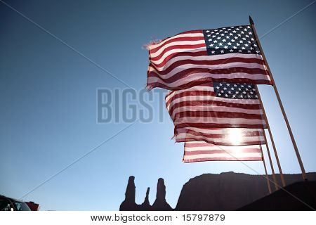 Four American flags waving over blue sky