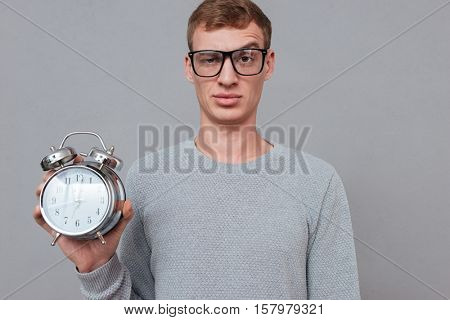 Young man in glasses showing clock in studio. looking at camera. isolated gray background