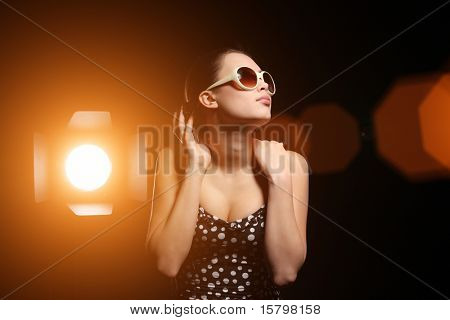 Studio portrait of beautiful woman with bright spotlight over black background