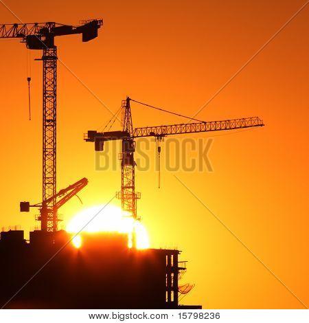 Industriebau-Krane und Gebäude Silhouetten über Sonne bei Sonnenaufgang.