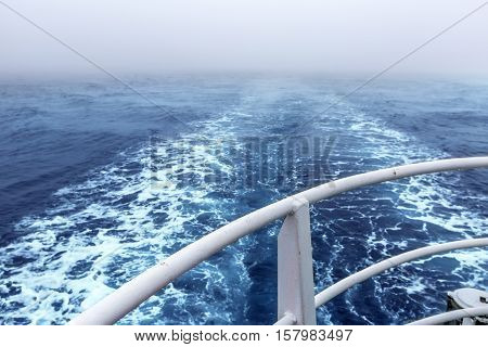 Trail on water surface behind of the ship in heavy fog