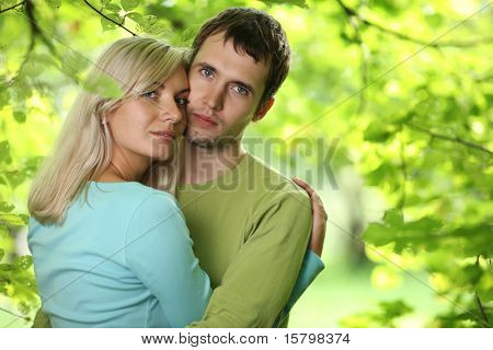 Closeup portrait of young couple in love outdoors, hugging over green foliage background. Shallow DOF.