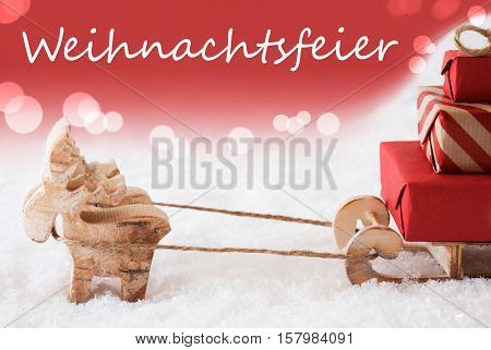 German Text Weihnachtsfeier Means Christmas Party. Moose Is Drawing A Sled With Red Gifts Or Presents In Snow. Christmas Card For Seasons Greetings. Red Christmassy Background With Bokeh Effect.