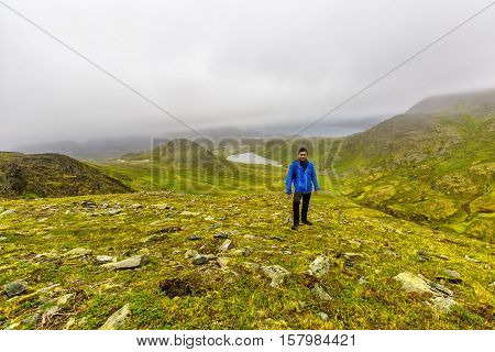 Young man standing on Kvanangen mountain watching at Skorpa uninhabited island in Troms country Norway.