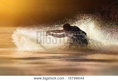 Waterskier silhouette moving fast in splashes of water at sunset