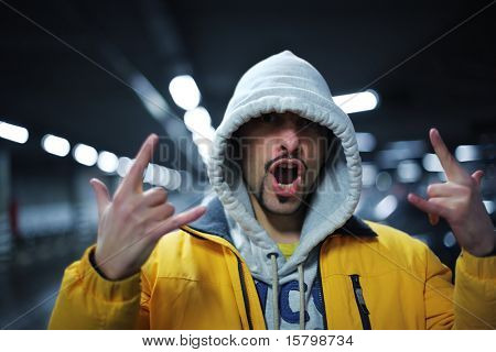 Portrait of young man in hoodie showing intimidating gesture. Shallow DOF.