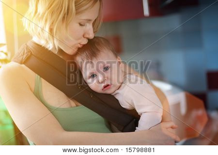 Mother carrying baby in sling and kissing. Indoors.