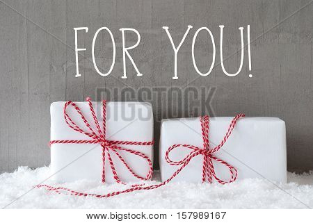 English Text For You. Two White Christmas Gifts Or Presents On Snow. Cement Wall As Background. Modern And Urban Style. Card For Birthday Or Seasons Greetings.