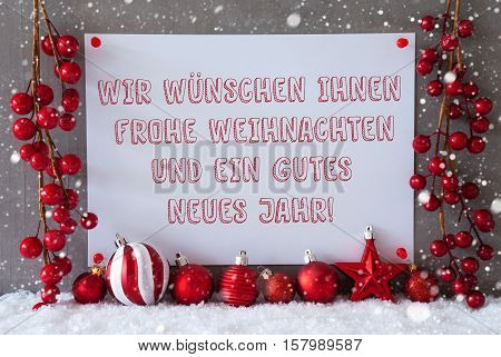 Label With German Text Wir Wuenschen Frohe Weihnachten Und Ein Gutes Neues Jahr Means Merry Christmas And Happy New Year. Red Decoration Like Balls On Snow. Cement Wall As Background With Snowflakes.