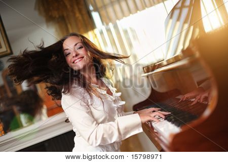 Happy young woman playing piano indoors. Closeup, shallow DOF.